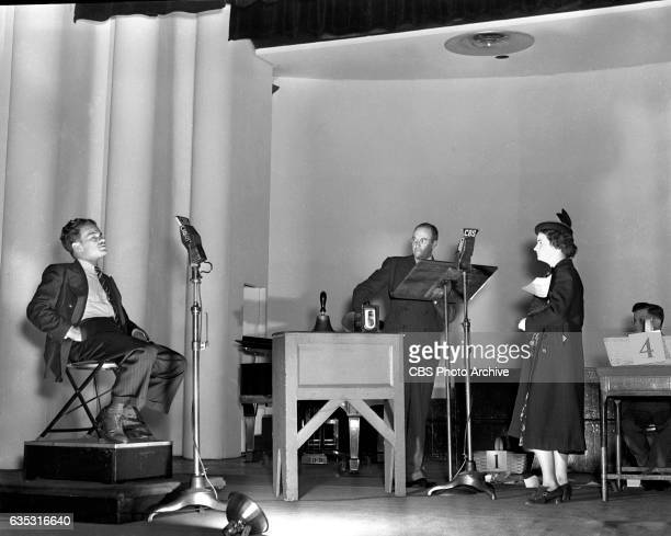 Jim McWilliams center host of 'The AskIt Basket' the CBS Radio quiz program during broadcast with contestants New York NY Image dated September 28...