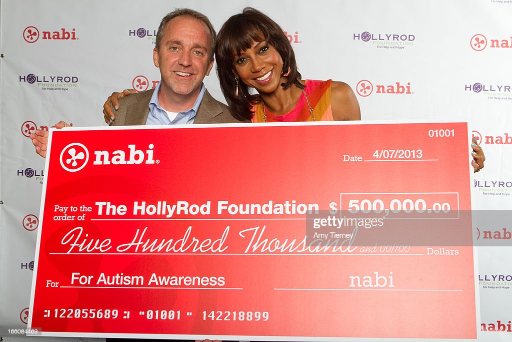 Jim Mitchell, CEO of Fuhu Inc., and Holly Robinson Peete gather for a donation on behalf of nabi to the HollyRod Foundation to help families living with autism at Fuhu, Inc. on April 7, 2013 in Los Angeles, California.