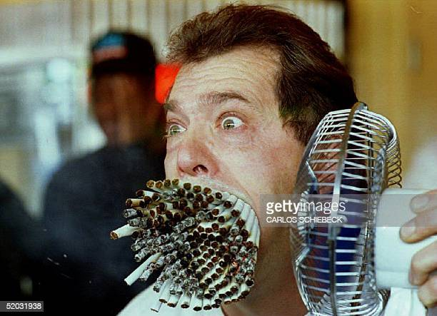 Jim Mouth uses a fan to blow smoke from 155 cigarettes as he breaks 'The Guinness Book of World Records' record 18 November 1993 for smoking the most...