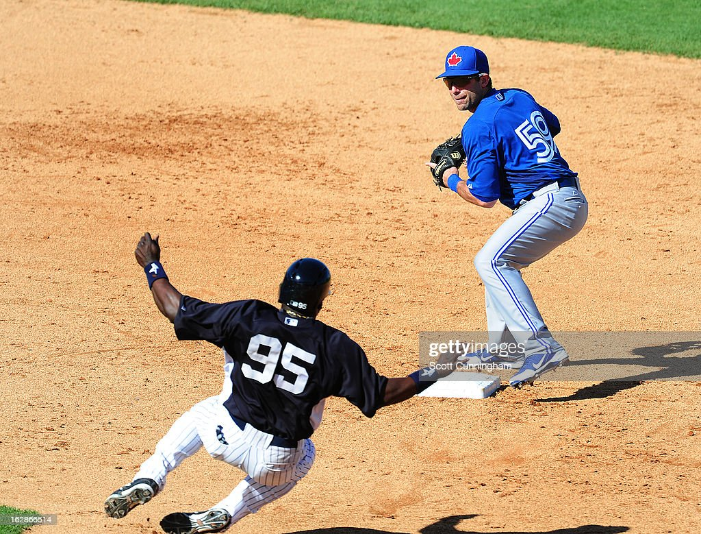 Jim Negrych #59 of the Toronto Blue Jays turns a game-ending double play against Ronnier Mustelier #95 of the New York Yankees during a spring training game at George M. Steinbrenner Field on February 28, 2013 in Tampa, Florida.