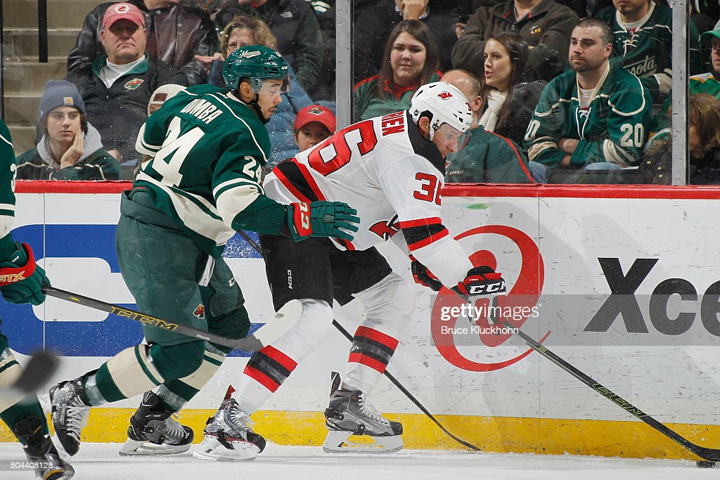 Jim O'Brien of the New Jersey Devils controls the puck along the boards with Matt Dumba of the Minnesota Wild defending during the game on January 10...
