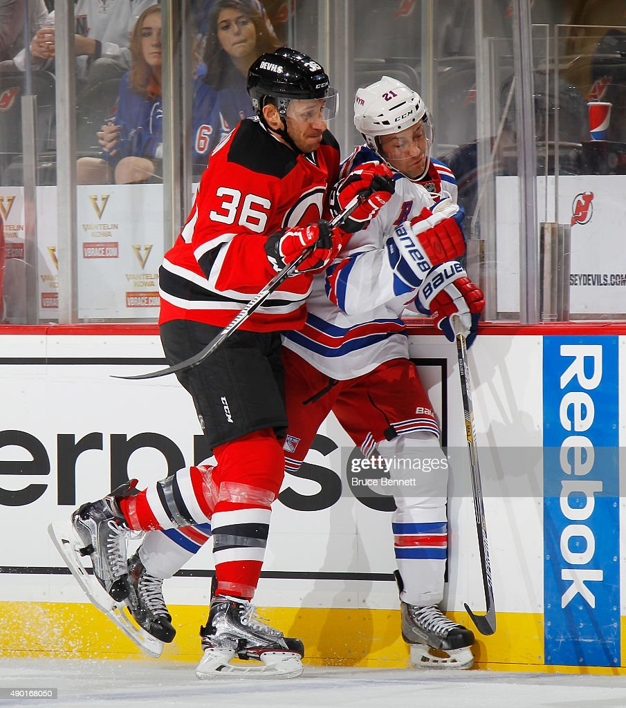 Jim O'Brien of the New Jersey Devils hits Derek Stepan of the New York Rangers into the boards during the first period during a preseason game at the...