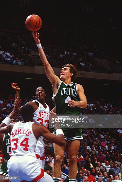 Jim Paxson of the Boston Celtics lays the ball up over Charles Shackleford and Chris Morris of the New Jersey Nets during an NBA basketball game...