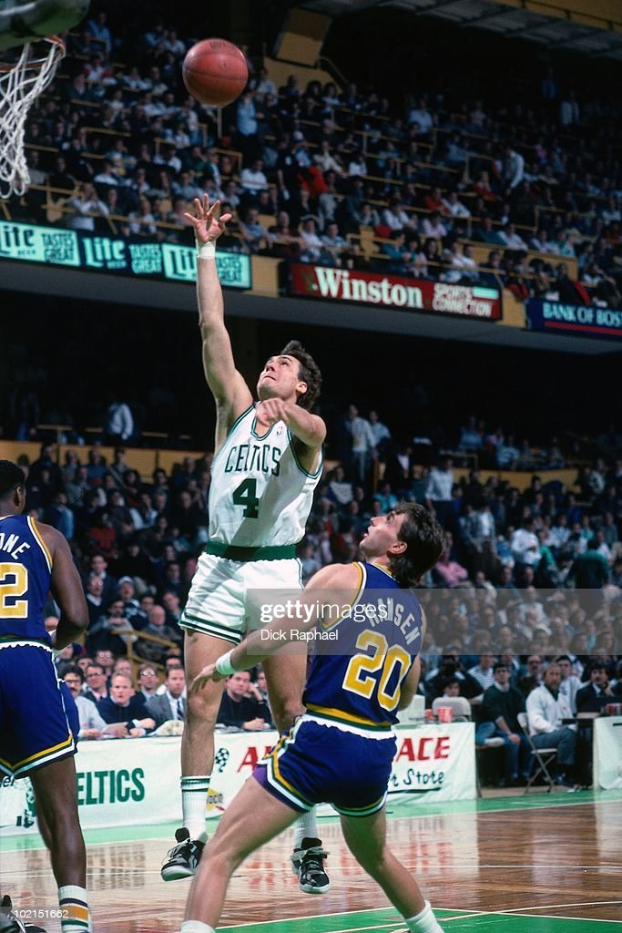 Jim Paxson #4 of the Boston Celtics shoots a layup against Bobby Hanson #20 of the Utah Jazz during a game played in 1990 at the Boston Garden in Boston, Massachusetts.