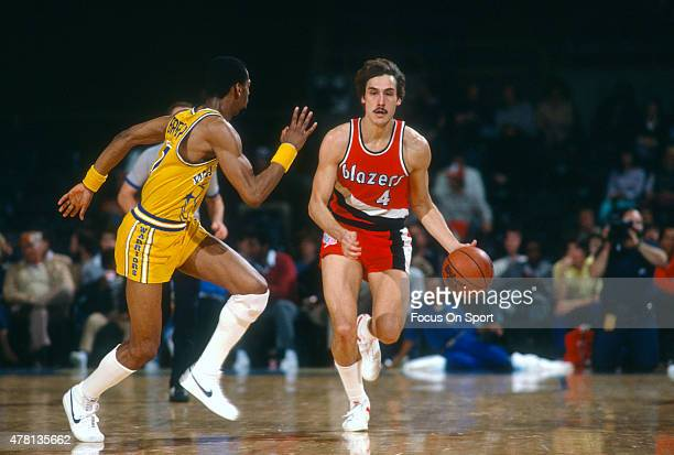 Jim Paxson of the Portland Trail Blazers dribbles the ball up court while defended by Ron Brewer of the Golden State Warriors during an NBA...