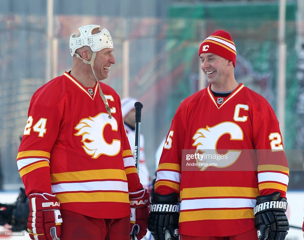 Jim Peplinski #24 and Joe Nieuwendyk #25 of the Calgary Flames Alumni chat before their game against the Montreal Canadiens Alumni during the Alumni game held as part of the 2011 NHL Heritage Classic festivities at McMahon Stadium on February 19, 2011 in Calgary, Alberta, Canada.