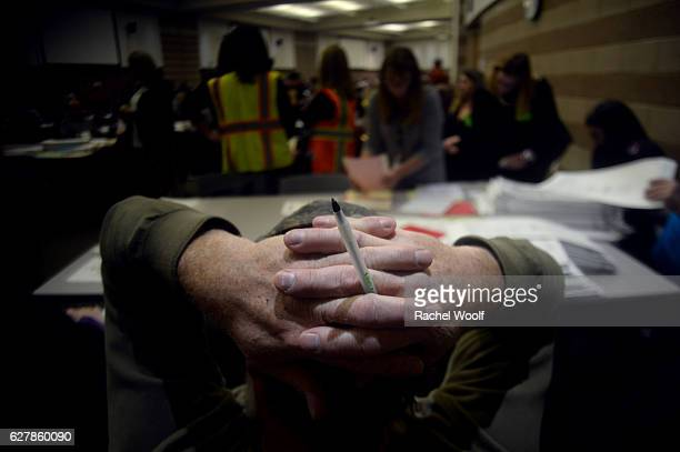 Jim Powers of Troy folds his hands over his head as he watches volunteers and city officials participate in a recount after a federal judge ordered...