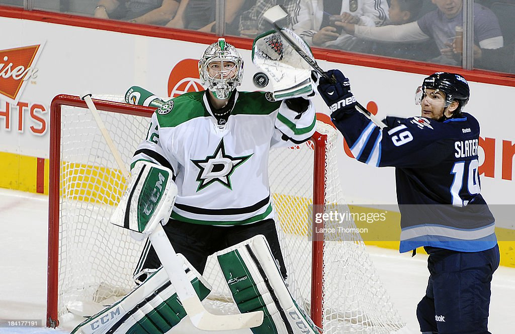 Jim Slater #19 of the Winnipeg Jets and goaltender Kari Lehtonen #32 of the Dallas Stars keep an eye on the puck as it flies in the air during second period action at the MTS Centre on October 11, 2013 in Winnipeg, Manitoba, Canada.