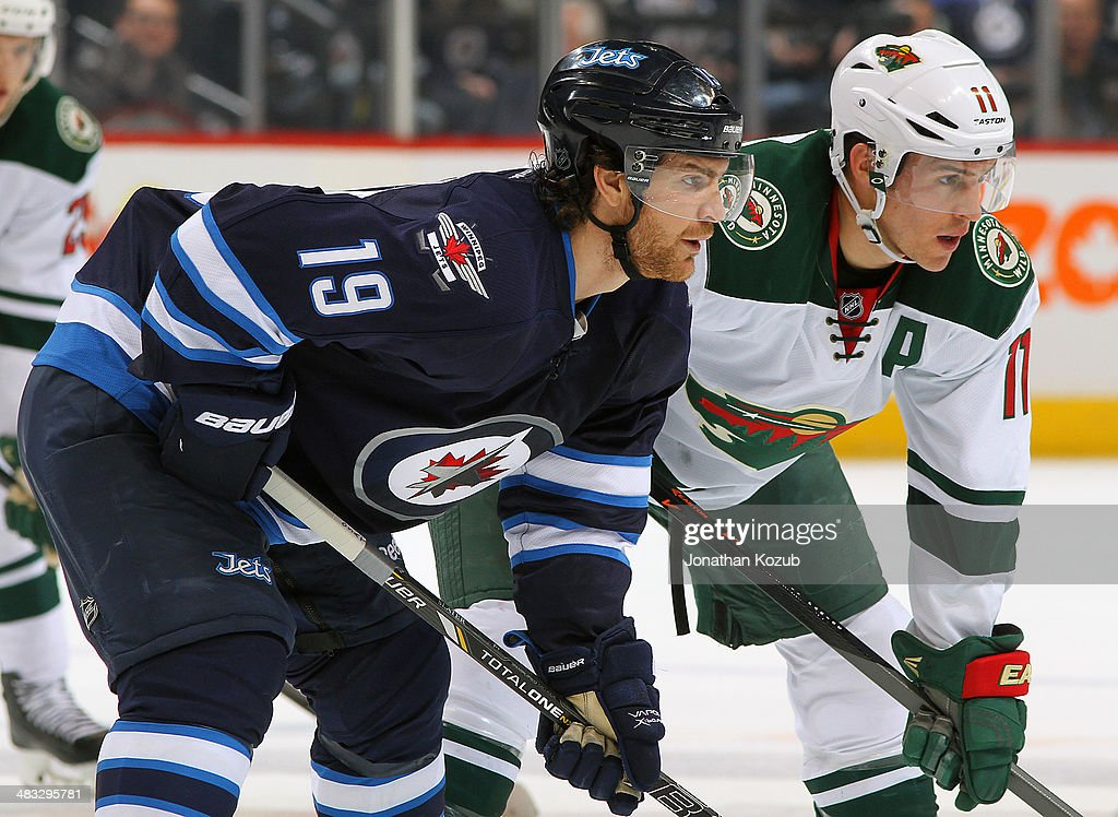 Jim Slater #19 of the Winnipeg Jets and Zach Parise #11 of the Minnesota Wild get set for a first-period faceoff at the MTS Centre on April 7, 2014 in Winnipeg, Manitoba, Canada. This game is the 500th of Slater's NHL career.