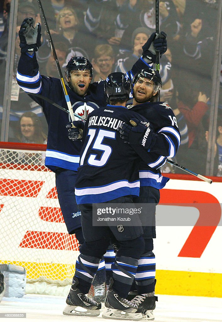 Jim Slater #19 of the Winnipeg Jets celebrates a second period goal against the Carolina Hurricanes with teammates <a gi-track='captionPersonalityLinkClicked' href=/galleries/search?phrase=Matt+Halischuk&family=editorial&specificpeople=714406 ng-click='$event.stopPropagation()'>Matt Halischuk</a> #15 and <a gi-track='captionPersonalityLinkClicked' href=/galleries/search?phrase=Eric+Tangradi&family=editorial&specificpeople=4361715 ng-click='$event.stopPropagation()'>Eric Tangradi</a> #27 at the MTS Centre on March 22, 2014 in Winnipeg, Manitoba, Canada.