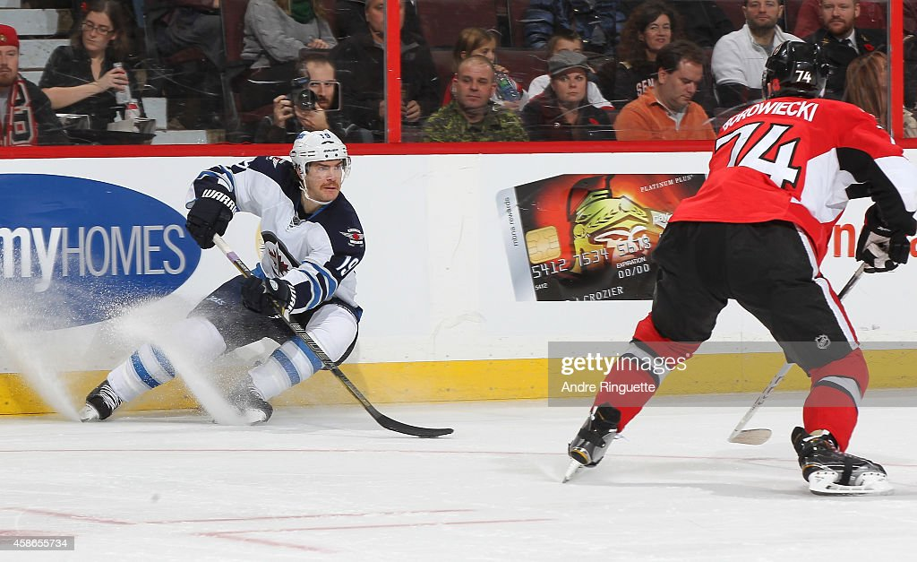 Jim Slater #19 of the Winnipeg Jets controls the puck against Mark Borowiecki #74 of the Ottawa Senators at Canadian Tire Centre on November 8, 2014 in Ottawa, Ontario, Canada.