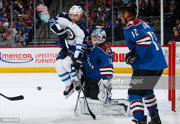 Jim Slater of the Winnipeg Jets leaps to avoid the puck as goalie Reto Berra of the Colorado Avalanche defends the goal against the shot at Pepsi...