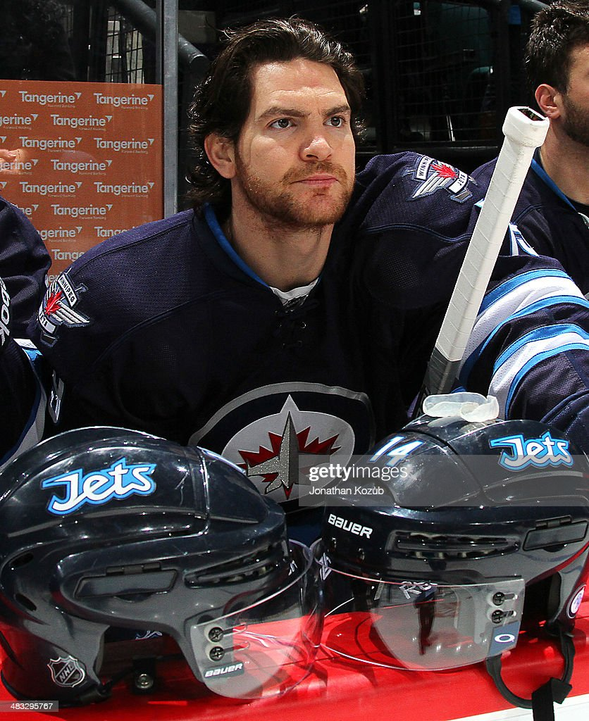 Jim Slater #19 of the Winnipeg Jets looks on from the bench prior to puck drop against the Minnesota Wild at the MTS Centre on April 7, 2014 in Winnipeg, Manitoba, Canada. This game is the 500th of Slater's NHL career.