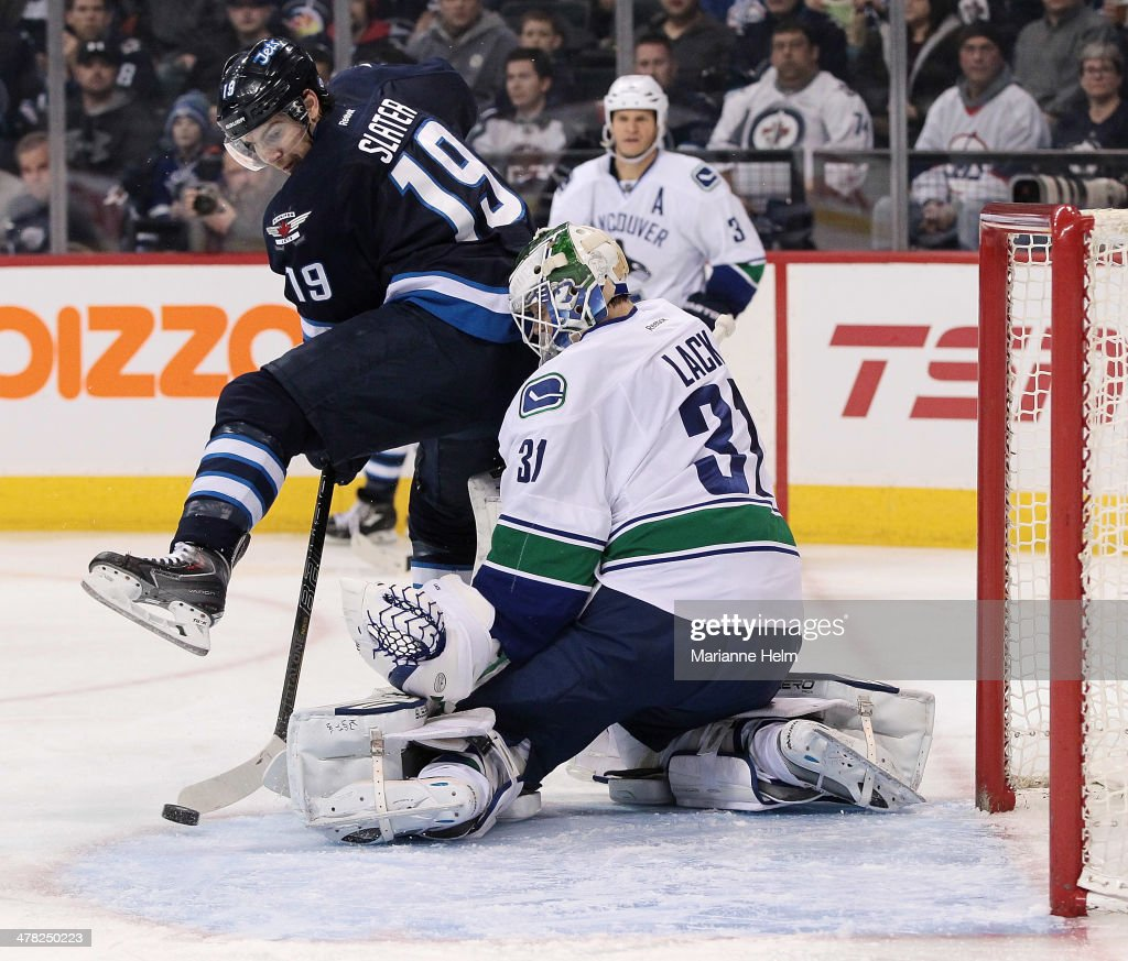 Jim Slater #19 of the Winnipeg Jets tries to get the puck past Eddie Lack #31 of the Vancouver Canucks in second-period action in an NHL game at the MTS Centre on March 12, 2014 in Winnipeg, Manitoba, Canada.