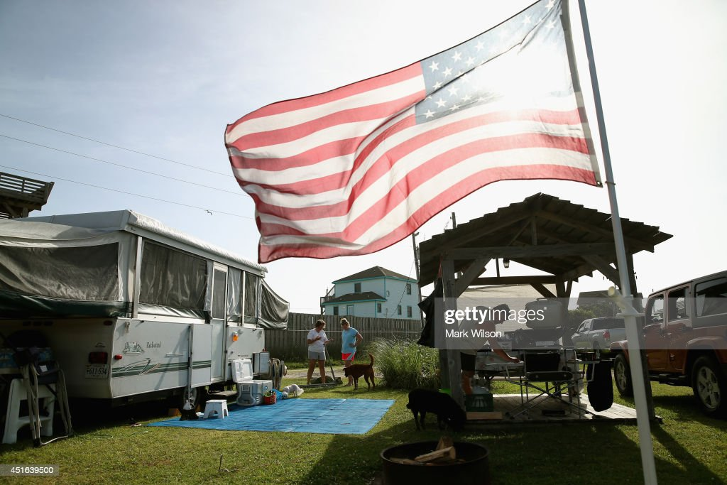 Jim Sullivan of Fredericksburg Va. breaks down his campsite while his wife (L) Amy Sullivan and daughter Stephanie (2nd-L) help, at the KOA Capmground to complying with the mandatory evacuation orders for Hatteras Island, July 3, 2014 in Rodanthe, North Carolina. A Hurricane warning has been issued for North Carolina's Outer Banks due to approaching Tropical Storm Arthur that is expected to gain strength and become a category 1 hurricane before it passes the area.