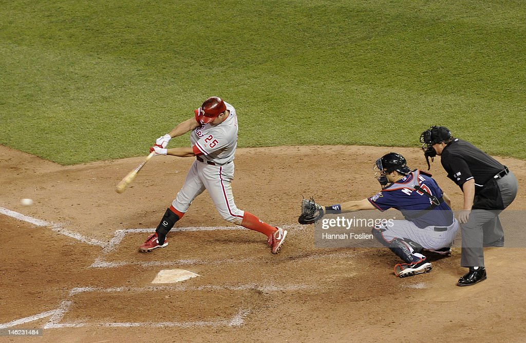 <a gi-track='captionPersonalityLinkClicked' href=/galleries/search?phrase=Jim+Thome&family=editorial&specificpeople=202878 ng-click='$event.stopPropagation()'>Jim Thome</a> #25 of the Philadelphia Phillies hits an RBI single as <a gi-track='captionPersonalityLinkClicked' href=/galleries/search?phrase=Joe+Mauer&family=editorial&specificpeople=214614 ng-click='$event.stopPropagation()'>Joe Mauer</a> #7 of the Minnesota Twins defends home plate and umpire Gerry Davis #12 calls balls and strikes during the sixth inning on June 12, 2012 at Target Field in Minneapolis, Minnesota.