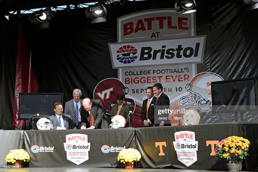 Jim Weaver, Virginia Tech Athletic Director, signs a contract as (L-R) Marcus Smith, President/COO Speedway Motorsports, <a gi-track='captionPersonalityLinkClicked' href=/galleries/search?phrase=Frank+Beamer&family=editorial&specificpeople=234759 ng-click='$event.stopPropagation()'>Frank Beamer</a>, Virginia Tech Head Coach, Dave Hart, Tennessee Vice Chancellor/Athletic Director, Butch Jones, Tennessee Head Coach, and Jerry Caldwell, General Manager Bristol Motor Speedway, look on at Bristol Motor Speedway on October 14, 2013 in Bristol, Tennessee. Bristol Motor Speedway plans to transform the legendary Speedway into the world's largest football stadium for the inaugural Battle at Bristol, to be held on Saturday, September 10, 2016. The event will feature a game between the Virginia Tech Hokies and Tennessee Volunteers and is projected to set the NCAA record for highest single-game attendance.