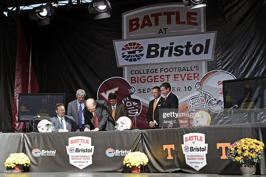 Jim Weaver, Virginia Tech Athletic Director, signs a contract as (L-R) Marcus Smith, President/COO Speedway Motorsports, Frank Beamer, Virginia Tech Head Coach, Dave Hart, Tennessee Vice Chancellor/Athletic Director, Butch Jones, Tennessee Head Coach, and Jerry Caldwell, General Manager Bristol Motor Speedway, look on at Bristol Motor Speedway on October 14, 2013 in Bristol, Tennessee. Bristol Motor Speedway plans to transform the legendary Speedway into the world's largest football stadium for the inaugural Battle at Bristol, College Football's Biggest EVER game to be held on Saturday, September 10, 2016. The event will feature a border battle between the Virginia Tech Hokies and Tennessee Volunteers and is projected to set the NCAA record for highest single-game attendance.
