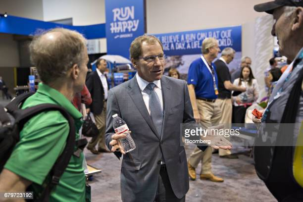 Jim Weber chairman and chief executive officer of Brooks Sports Inc center speaks with attendees on the exhibit floor during the Berkshire Hathaway...