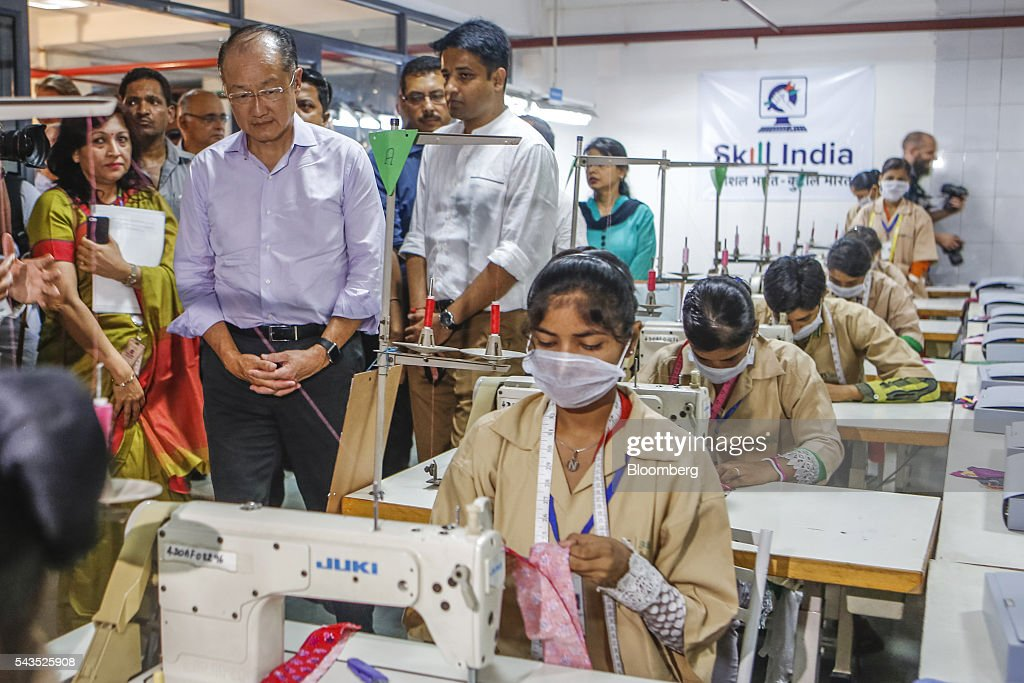 Jim Yong Kim president of the World Bank Group second left watches students sewing during visit to a vocational training class at the Infrastructure...