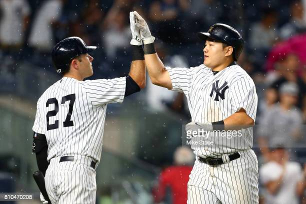 JiMan Choi of the New York Yankees celebrates with Austin Romine after hitting a 2run home run in the fourth inning against the Milwaukee Brewers at...