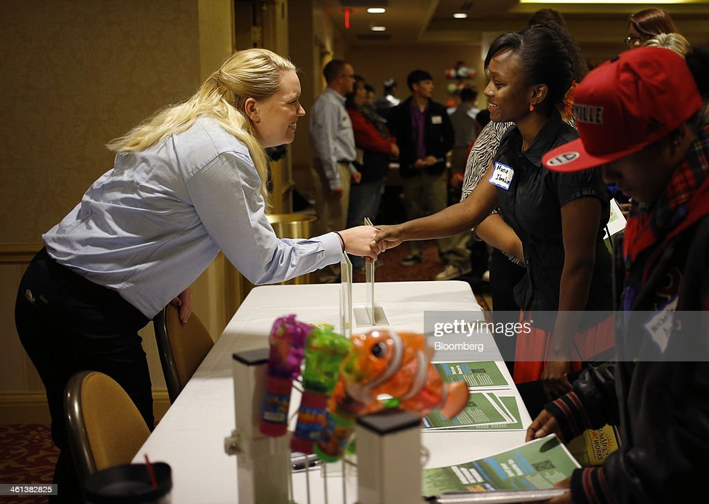 Jimi Pierce, group sales representative at Kentucky Kingdom Amusement Park, left, shakes hands with a prospective job applicant during a job fair to hire seasonal summer workers in Louisville, Kentucky, U.S. on Saturday, Jan. 4, 2014. Companies added more workers than projected in December as U.S. employers grew more optimistic about the prospects for demand, a private report based on payrolls showed Jan. 8. Photographer: Luke Sharrett/Bloomberg via Getty Images