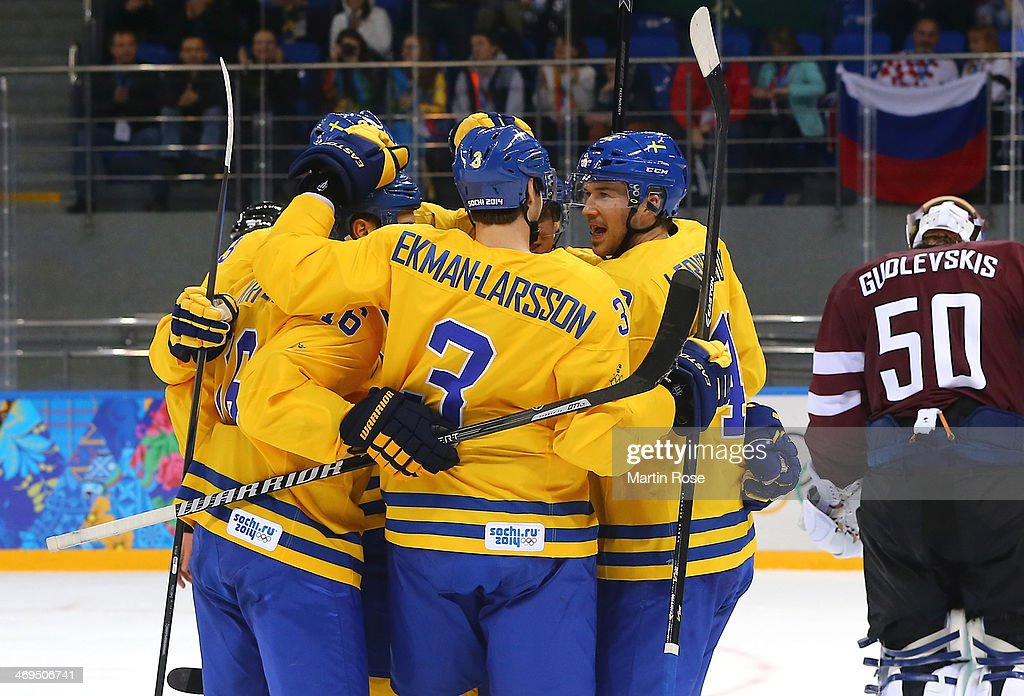 Jimmie Ericsson #42 of Sweden celebrates with teammates after scoring against Kristers Gudlevskis #50 of Latvia in the second period during the Men's Ice Hockey Preliminary Round Group C game on day eight of the Sochi 2014 Winter Olympics at Shayba Arena on February 15, 2014 in Sochi, Russia.