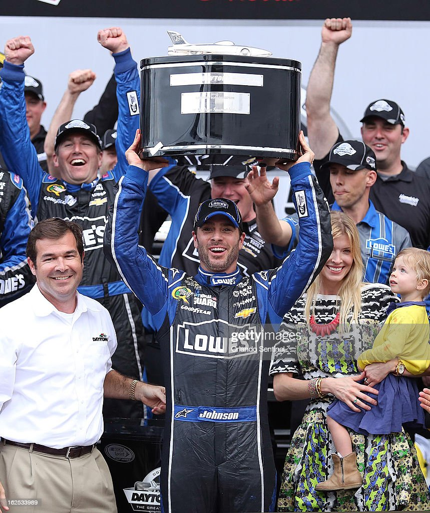 Jimmie Johnson celebrates in Victory Lane after winning the Daytona 500 race at Daytona International Speedway on Sunday, February 24, 2013. Johnson's wife, Chandra, and daughter, Genevieve Marie, are to the right. At left is track president Joie Chitwood III.