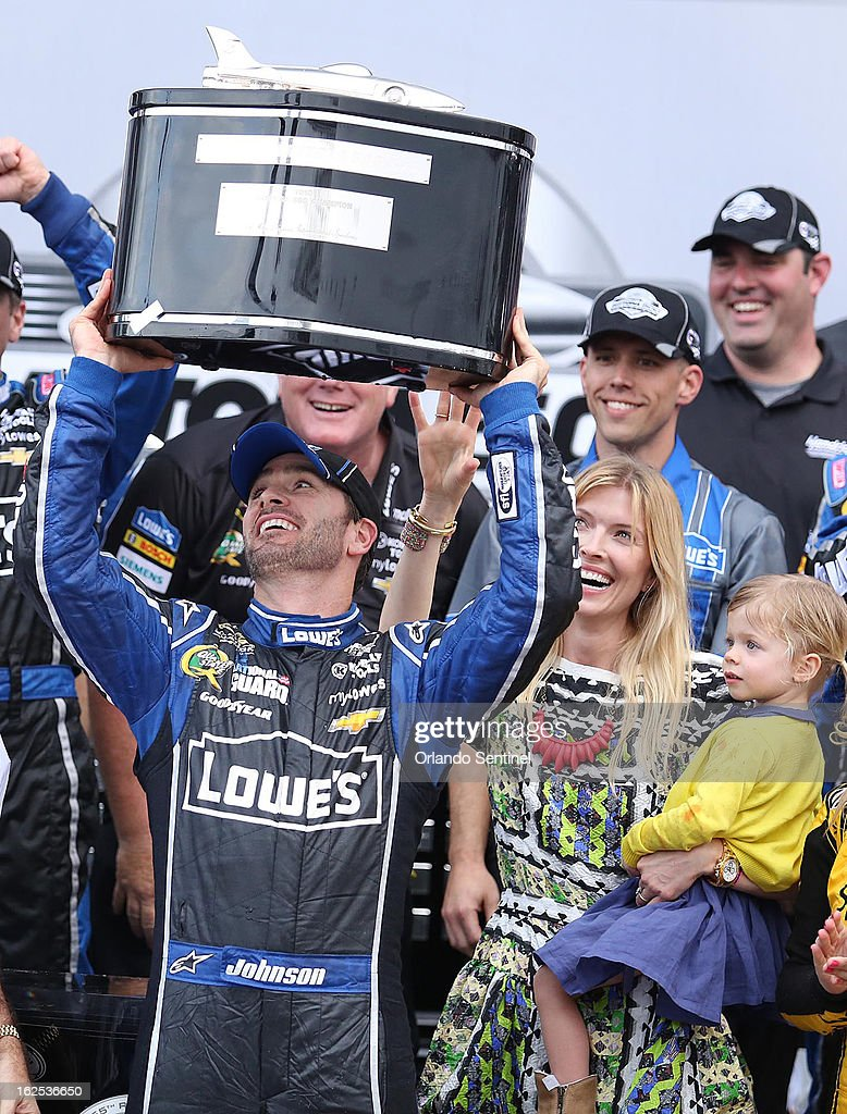 Jimmie Johnson celebrates in Victory Lane after winning the Daytona 500 race at Daytona International Speedway in Daytona Beach, Florida, Sunday, February 24, 2013. Jimmie's wife, Chandra (beside him at right) laughs as she holds their daughter, Genevieve Marie.