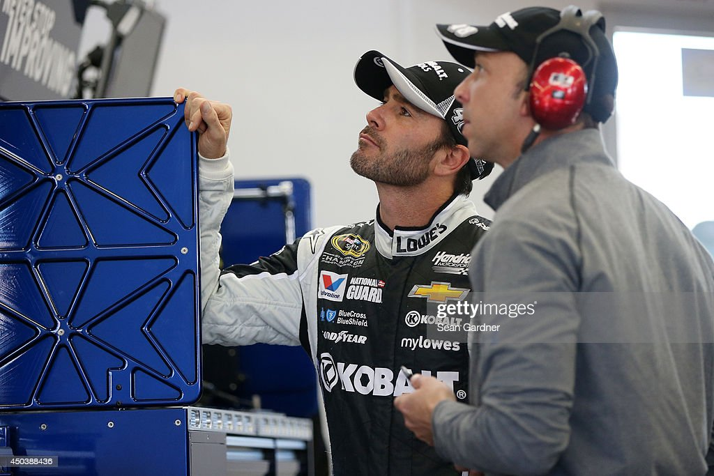 Jimmie Johnson, driver of the #48 Kobalt Tools Chevrolet, left, and crew chief Chad Knaus look at monitors in the garage area during practice for the NASCAR Sprint Cup Series Kobalt 400 at Las Vegas Motor Speedway on March 7, 2014 in Las Vegas, Nevada.