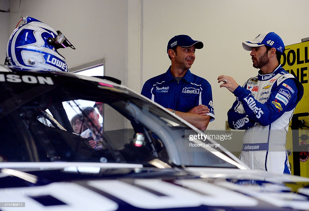 Jimmie Johnson, driver of the #48 Lowe's Chevrolet, and crew chief Chad Knaus speak in the garage during practice for the NASCAR Sprint Cup Series Daytona 500 at Daytona International Speedway on February 22, 2014 in Daytona Beach, Florida.