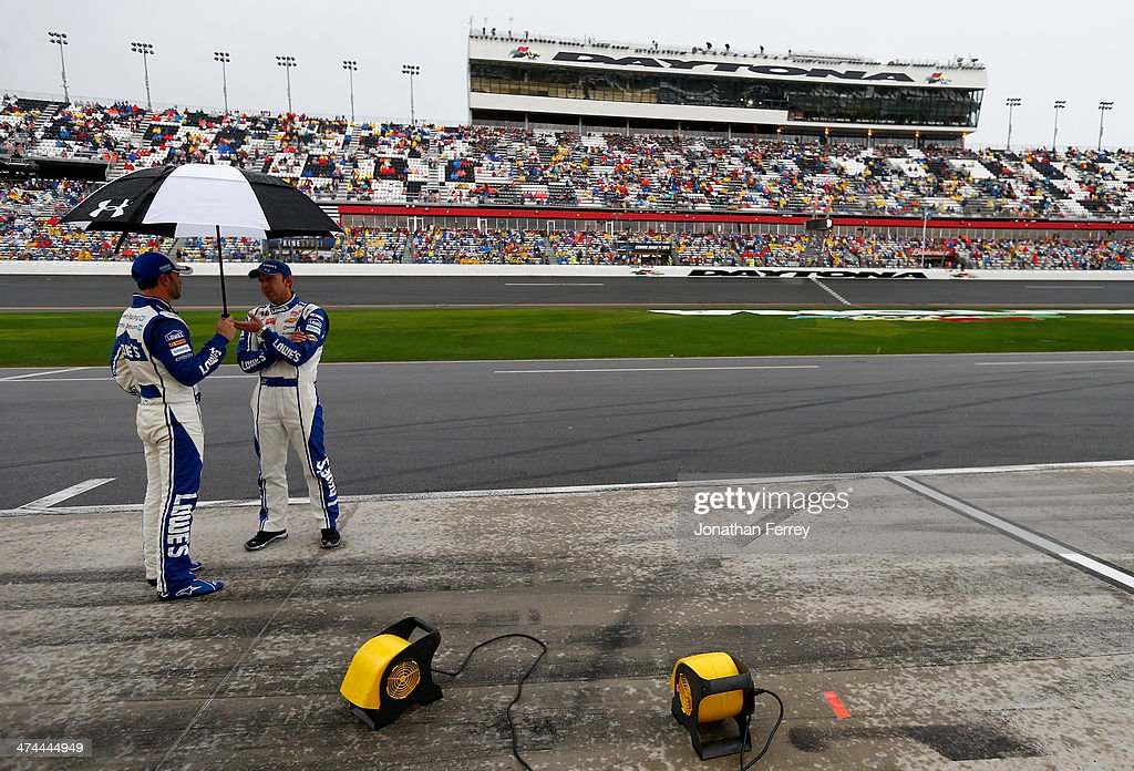 Jimmie Johnson, driver of the #48 Lowe's Chevrolet, and his crew chief Chad Knaus take cover under an umbrella on pit road during a rain delay in the NASCAR Sprint Cup Series Daytona 500 at Daytona International Speedway on February 23, 2014 in Daytona Beach, Florida.