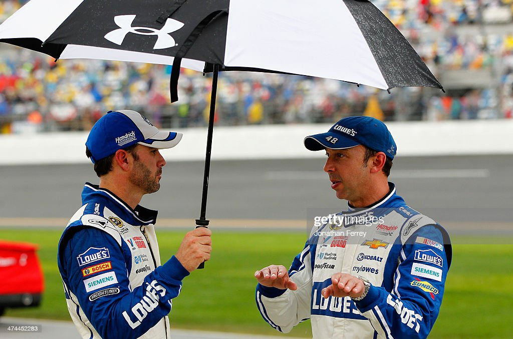 Jimmie Johnson, driver of the #48 Lowe's Chevrolet, and his crew chief Chad Knaus take cover under an umbrella during a rain delay in the NASCAR Sprint Cup Series Daytona 500 at Daytona International Speedway on February 23, 2014 in Daytona Beach, Florida.