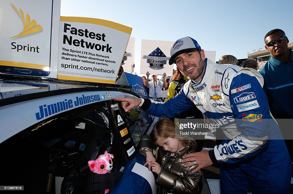 Jimmie Johnson, driver of the #48 Lowe's Chevrolet, and his daughter, Lydia, pose with the winner's decal in Victory Lane after winning the NASCAR Sprint Cup Series Folds of Honor QuikTrip 500 at Atlanta Motor Speedway on February 28, 2016 in Hampton, Georgia.