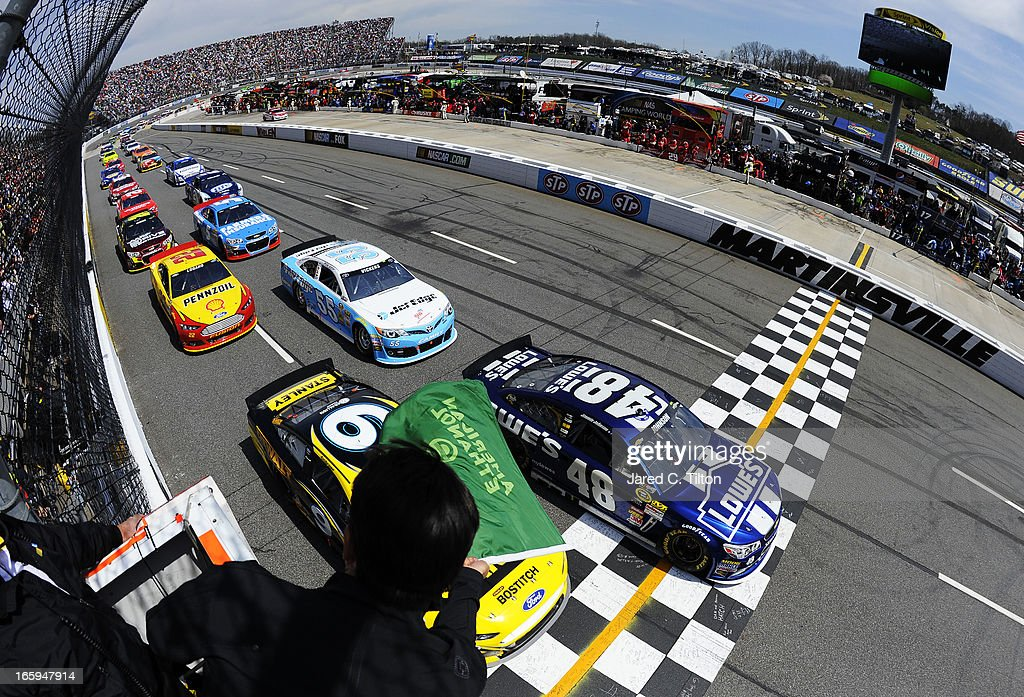 Jimmie Johnson, driver of the #48 Lowe's Chevrolet, and Marcos Ambrose, driver of the #9 Stanley Ford, lead the field past the green flag to start the NASCAR Sprint Cup Series STP Gas Booster 500 on April 7, 2013 at Martinsville Speedway in Ridgeway, Virginia.
