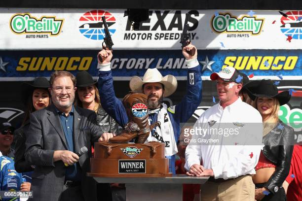 Jimmie Johnson driver of the Lowe's Chevrolet celebrates by shooting guns in Victory Lane after winning the Monster Energy NASCAR Cup Series O'Reilly...