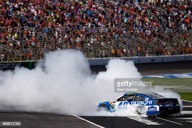 Jimmie Johnson driver of the Lowe's Chevrolet celebrates with a burnout after winning the Monster Energy NASCAR Cup Series O'Reilly Auto Parts 500 at...