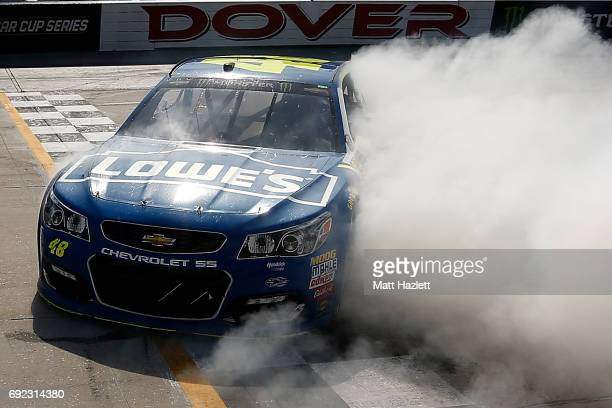 Jimmie Johnson driver of the Lowe's Chevrolet celebrates with a burnout after winning the Monster Energy NASCAR Cup Series AAA 400 Drive for Autism...