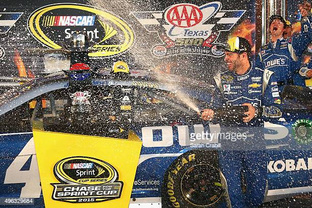 Jimmie Johnson driver of the Lowe's Chevrolet celebrates with champagne in Victory Lane after winning the NASCAR Sprint Cup Series AAA Texas 500 at...