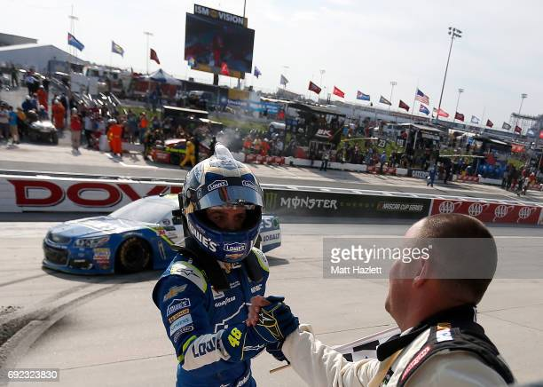 Jimmie Johnson driver of the Lowe's Chevrolet celebrates with NASCAR official Corey Richardson after winning the Monster Energy NASCAR Cup Series AAA...