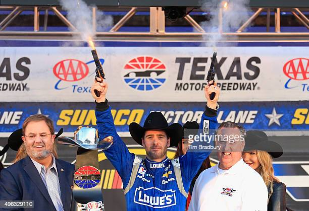 Jimmie Johnson driver of the Lowe's Chevrolet celebrates with pistols in Victory Lane after winning during the NASCAR Sprint Cup Series AAA Texas 500...