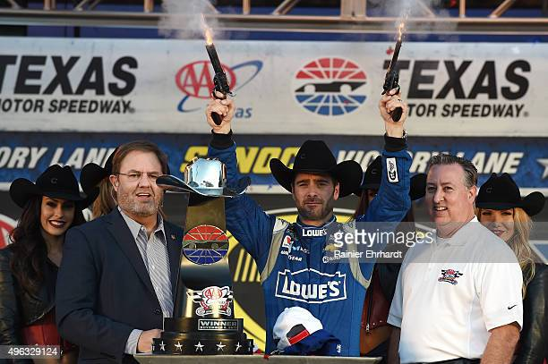 Jimmie Johnson driver of the Lowe's Chevrolet celebrates with pistols and Texas Motor Speedway President Eddie Gossage in Victory Lane after winning...