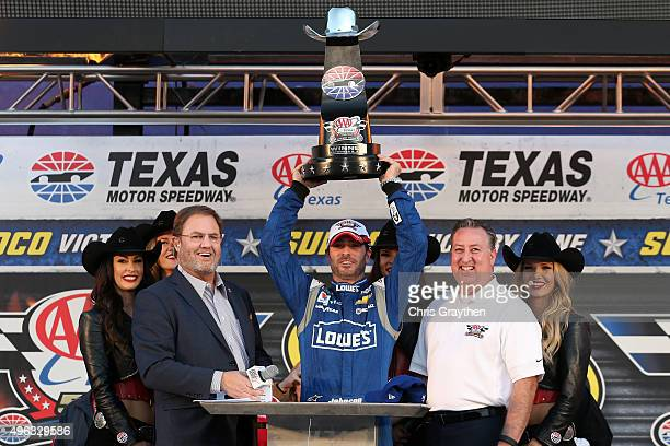 Jimmie Johnson driver of the Lowe's Chevrolet celebrates with the trophy and Texas Motor Speedway President Eddie Gossage in Victory Lane after...