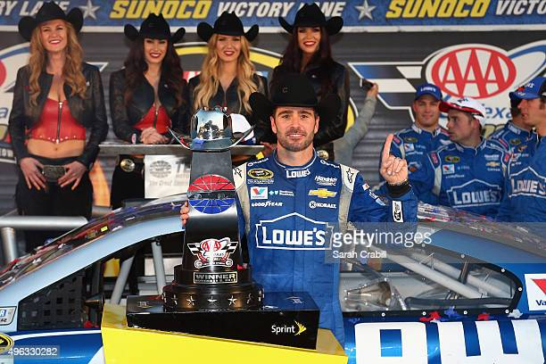 Jimmie Johnson driver of the Lowe's Chevrolet celebrates with the trophy in victory lane after winning the NASCAR Sprint Cup Series AAA Texas 500 at...