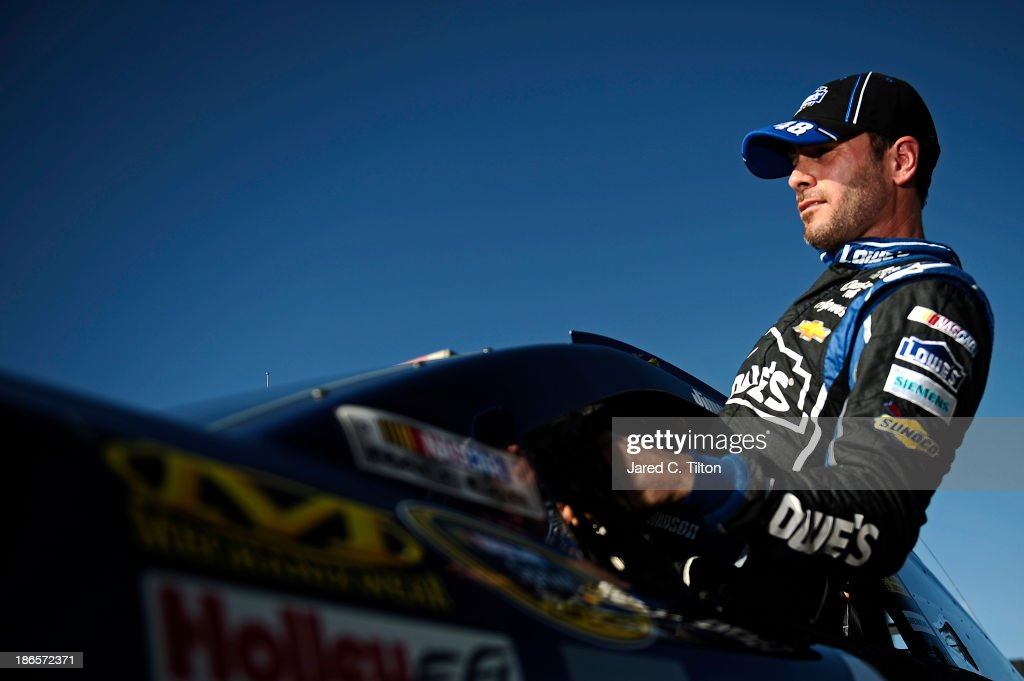 Jimmie Johnson, driver of the #48 Lowe's Chevrolet, climbs from his car after qualifying for the NASCAR Sprint Cup Series AAA Texas 500 at Texas Motor Speedway on November 1, 2013 in Fort Worth, Texas.