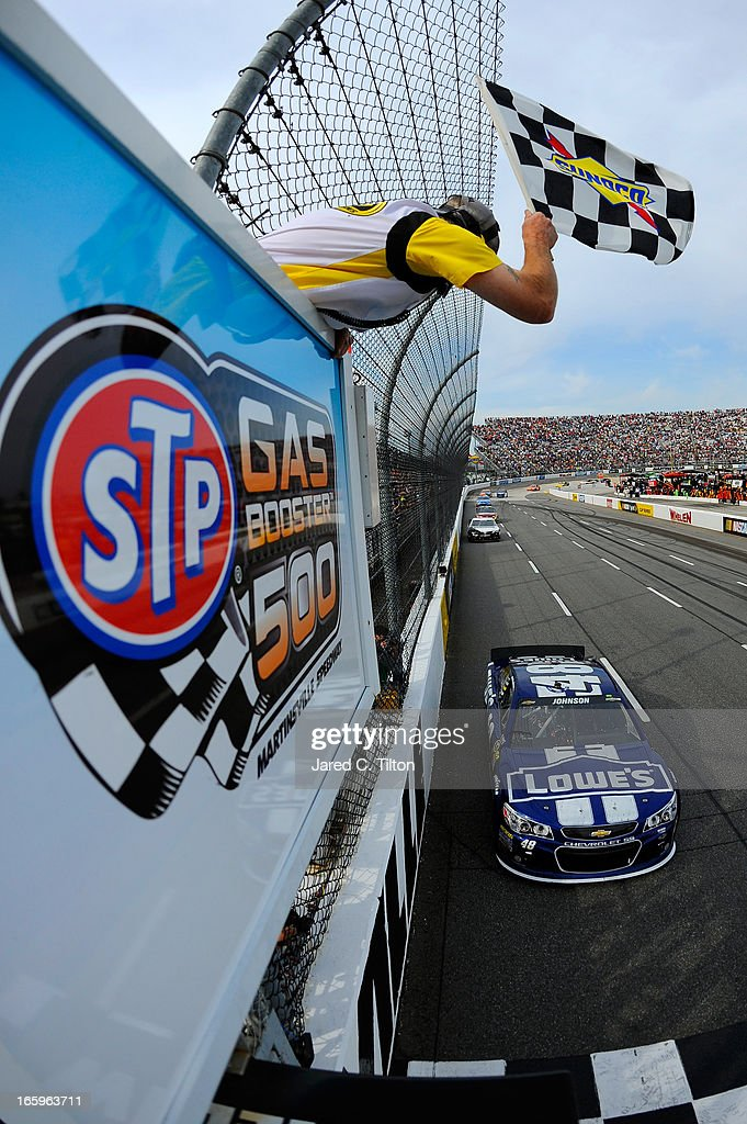 Jimmie Johnson, driver of the #48 Lowe's Chevrolet, crosses the finish line to win the NASCAR Sprint Cup Series STP Gas Booster 500 on April 7, 2013 at Martinsville Speedway in Ridgeway, Virginia.
