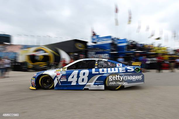 Jimmie Johnson driver of the Lowe's Chevrolet drives in the garage area during practice for the NASCAR Sprint Cup Series myAFibRiskcom 400 at...