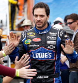 Jimmie Johnson driver of the Lowe's Chevrolet greets fans during driver introductions for the NASCAR Sprint Cup Series Auto Club 400 at Auto Club...