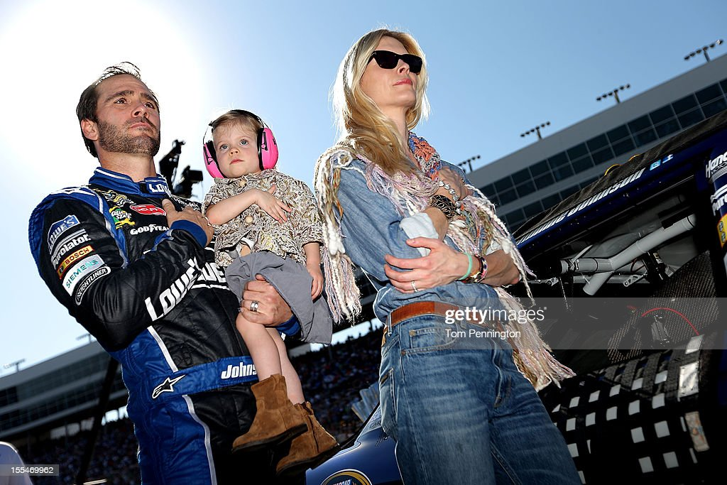 Jimmie Johnson, driver of the #48 Lowe's Chevrolet, holds daughter Genevieve Marie as wife Chandra looks on during the National Anthem prior to the start of the NASCAR Sprint Cup Series AAA Texas 500 at Texas Motor Speedway on November 4, 2012 in Fort Worth, Texas.