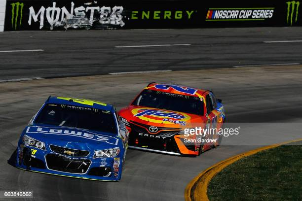 Jimmie Johnson driver of the Lowe's Chevrolet leads Matt Kenseth driver of the Tide Pods Toyota during the Monster Energy NASCAR Cup Series STP 500...
